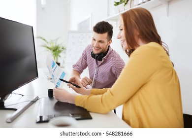 business, startup and people concept - happy creative team with papers and computer at office