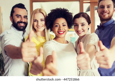 business, startup, people and teamwork concept - happy creative team showing thumbs up in office