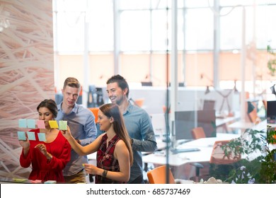 business, startup, planning, management and people concept - happy creative team writing on stickers at office glass board in modern coworking space.