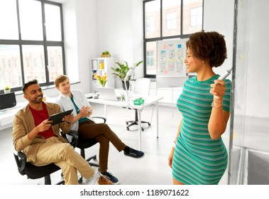 business, startup, planning and people concept - woman at glass board showing something to creative team at office presentation