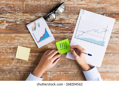 business, statistics and people concept - close up of female hands with charts and eyeglasses on table