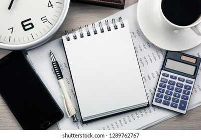 business still life from a notepad, a smartphone, a clock, a cup of coffee, a calculator top view