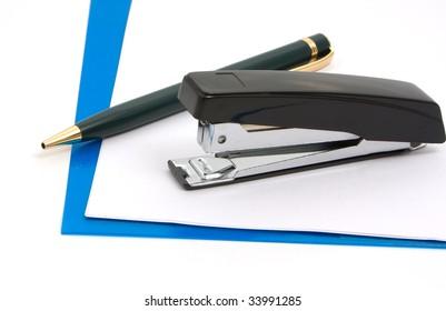 Business a still-life - black stapler, pen  and blue folder on white background