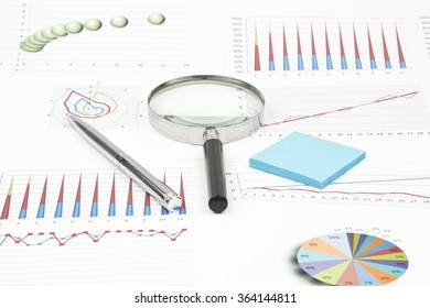 Business still-life of a diagram, magnifier, shiny pen, sticker