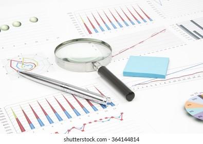 Business still-life of a diagram, magnifier, shiny pen, sticker