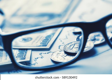 Business still-life with glasses dollars and schedule toned in blue
