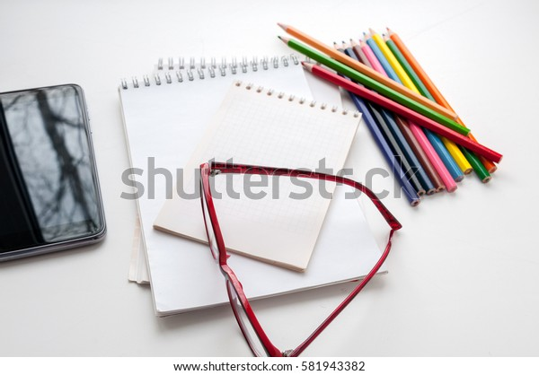 Business still-life, glasses, smart phone, notebook and colored pencils