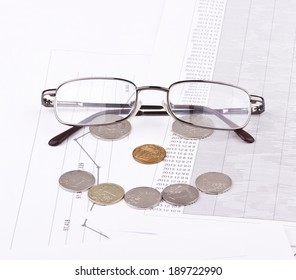 Business still-life of a graph, eyeglasses, coins, smile