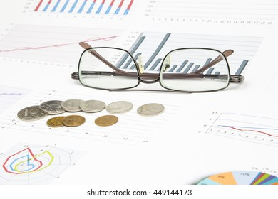 Business still-life of a graph, eyeglasses, coins