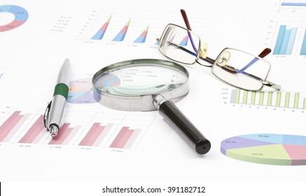 Business still-life of graph, eyeglasses, magnifier, shiny pen
