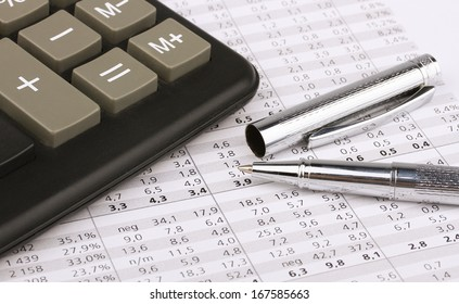 Business still-life of pen, charts, calculator, tables