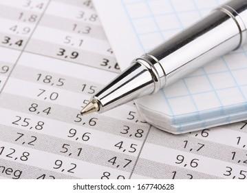 Business still-life of shiny pen, notebook, tables