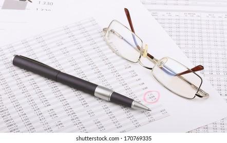 Business still-life from the table, eyeglasses, blue pen