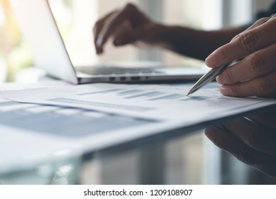 Business strategy analysis concept. Businessman with pen in hand working on laptop computer reviewing business marketing report, spreadsheet on desk in office, copy space, close up. toned image