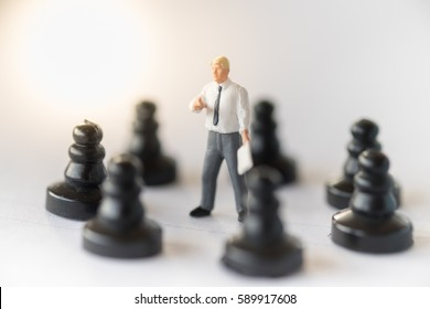 Business and strategy concept. Businessman miniature figure standing on center of circle of chess pieces