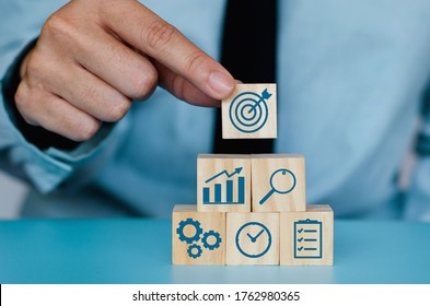 Business strategy concept. Hand arranging symbol with goal icon on wood cube block,Set target, Research and Plan,Teamwork.