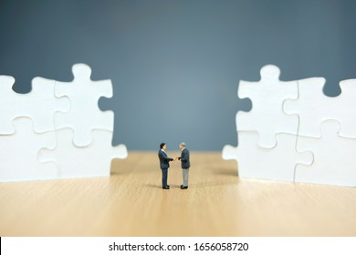 Business strategy conceptual photo - Miniature businessman make handshake partnership in the center of jigsaw puzzle piece that are arranged