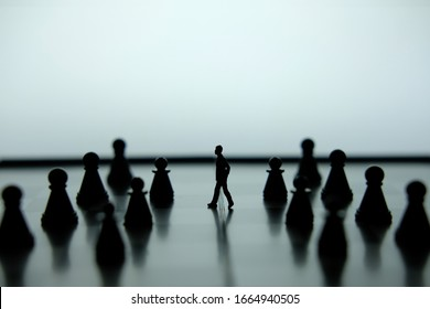 Business strategy conceptual photo - Miniature of businessman walking forward in the middle of chess piece on a chessboard