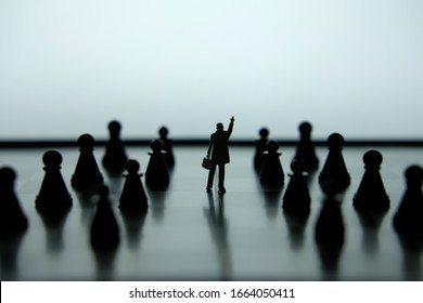 Business strategy conceptual photo - Silhouette of miniature of businessman pointing upside in the middle of chess piece on a chessboard