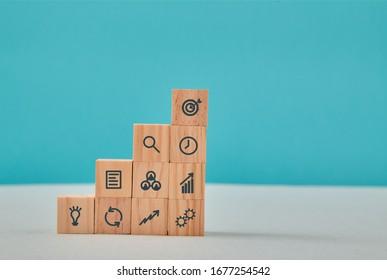 Stratégie commerciale et croissance. Efficacité et prévision. Échelle de carrière. Pyramide de cubes en bois avec panneaux de gestion
