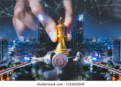 Business strategy ideas concept with chess board game on city background.Double exposure of the businessman hold a chess king on hand with cityscape image.
