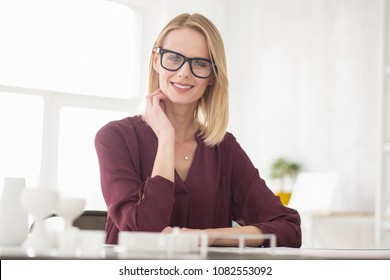 Business strategy. Jolly cheerful businesswoman wearing glasses while grinning to camera