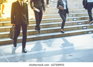 Business street in big city.After office work.In front of corporate building.Businessman walking quick steps.Some person hold business briefcase go down from stairs.Some person commute to home by car.