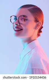 Business style. Portrait of a beautiful smiling young woman in elegant glasses and white shirt. Glasses fashion.