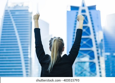 Business success - Celebrating businesswoman overlooking the city center high-rises.