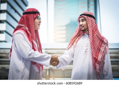 Business success concept. Arab businessman making handshake or holding hand together to agree joint business and partnership.