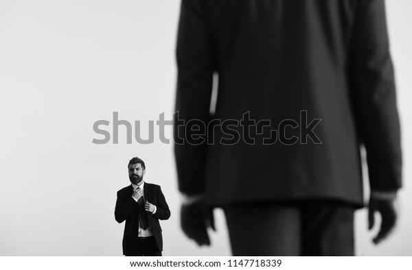 Business and success concept. Businessman adjusts tie. Man with beard and serious face looks forward at colleague in foreground, close up. Managers wear smart suits and ties on blue sky background.