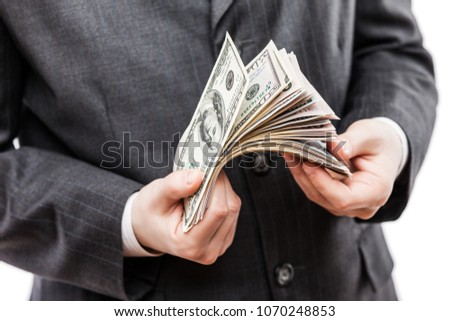 Business success concept - businessman in black suit hand holding US dollar currency money cash