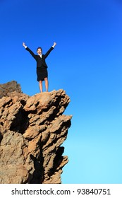 Business success concept. Businesswoman on top of mountain winning overcoming adversity and challenges. Successful young multiracial business woman in suit outdoors in nature.