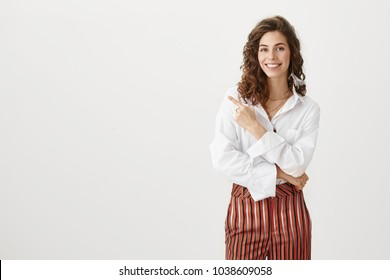 Business and success concept. Portrait of attractive influential girl smiling broadly while indicating left with forefinger, wearing stylish white blouse and striped trousers, standing over gray wall