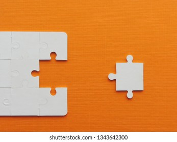 Business success concept,White puzzle pieces on orange background.