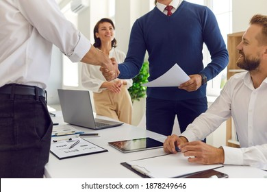 Business success, deal, cooperation decision concept. Smiling business partners colleagues sitting and looking at head managers handshake after successful negotiations, brainstorming