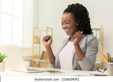 Business Success. Excited Black Businesswoman Sitting At Laptop Shaking Fists In Modern Office.