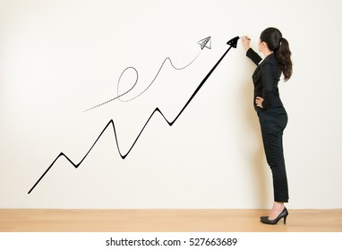 Business success growth chart. Business woman drawing graph showing profit growth on white wall. Asian mixed race businesswoman isolated on white background in suit.