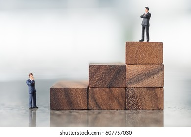 Business, Success and Growth concept. Two businessman miniature figures stand on the top of stack of wooden toy blocks and stand on ground thinking and looking to top of wood stack.