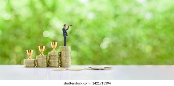 Business success, new challenge, new opportunity concept : Successful Business tycoon searches or finds for another challenged project after win many prizes. Golden trophy cup on rows of rising coins.