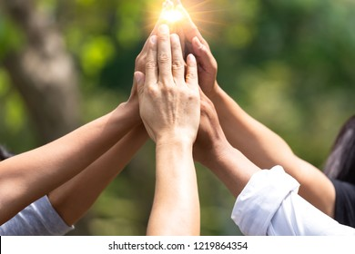 Business  success Team which hand of the work force combine power tag team with light and Group of diversity people hand assembly high five together for good teamwork.