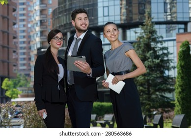 Business success. Three confident and motivated business partners are looking forward and discussing issues of business project. All are wearing formal suits. Outdoor business concept