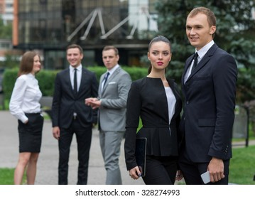 Business success. Two  confident and motivated business partners are working on the project. Both  are wearing formal suits. Outdoor business concept. Their motivated colleagues are on the background