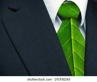 Business suit and green leaves as tie representing a natural job in defense of a green environment.