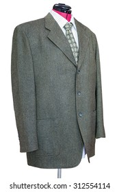 business suit on tailor mannequin - green tweed jacket with shirt and tie isolated on white background