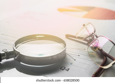 Business summary reports and a magnifying glass with glasses  on table office. Concept of Data Analysis, Investment Planning, Business Analytics.