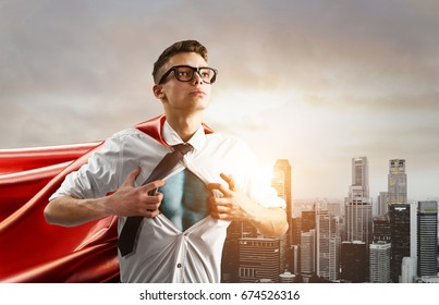 Business superhero. Young businessman showing super hero suit under his shirt down town on sunset.