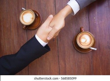 Business talk and hands shake at a coffee shop with two cups of latte.