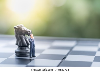 Business, target, decision and competition concept. Two businessman miniature figure standing on chessboard with black and knight chess pieces.