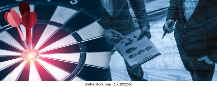 Business Target Goal For Success Strategy Concept - Red dart arrow hitting center goal on the dart board with business people working in background showing precision and success of business target.